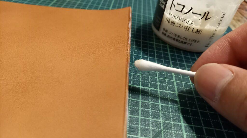 革の断面のコバに、綿棒で仕上剤をつけているところの画像